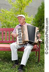 Accordion - Old man enjoying playing accordion in his garden