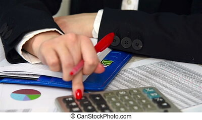 Accountant Calculates Profit And Writes On Notepad. Close Up