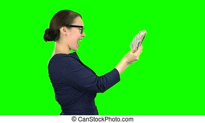 Accountant holds paper money in his hands and considers them. Green screen. Side view