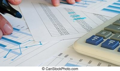 Accountant is checking financial results. Close up of paper...