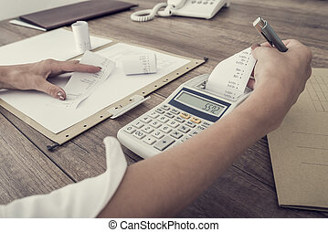 Retro image of accountant or businesswoman balancing the books checking the figures on a ledger with an adding machine , close up view of her hands and paperwork.