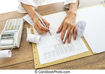Accountant or financial adviser checking and comparing receipts and statistical data while making a final report