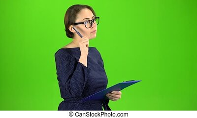 Accountant records the data in a paper tablet. Green screen...