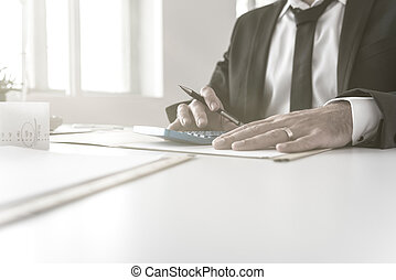 Accountant  working on his accounts using blue calculator