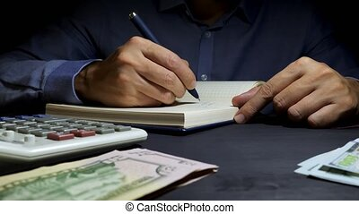 Accountant writing in the accounting book financial figures....
