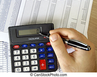Accounting - hand with pen and calculator on office desk