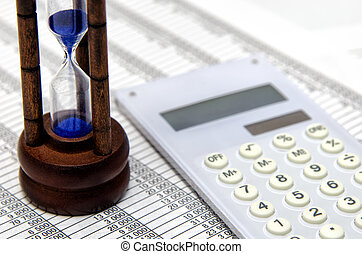 Hourglass and accounting documents and calculator