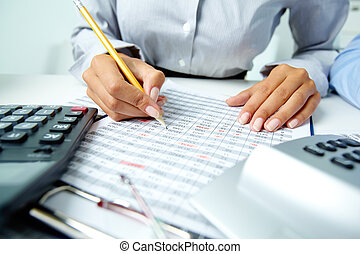 Photo of human hands holding pencil and ticking data in documents