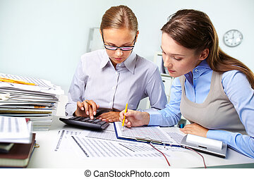Accounting report - Concentrated business women reviewing...