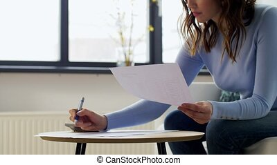 accounting, taxes and finances concept - young woman with papers and calculator at home
