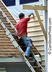 Young carpenter remodels aging home. He is installing siding and is using a level to be sure installation is precise. He is standing on a ladder on rooftop.