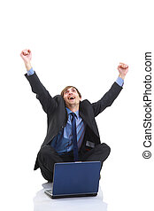 Achievement - Business success as a man raises his hands while looking at his laptop , isolated on white