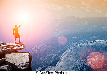 Achievement - Man standing on top of a cliff with arm raised