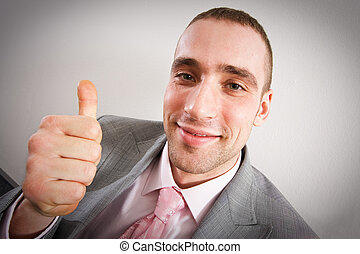 Achievement - thumbs up - Young businessman showing thumbs...