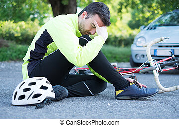 aching man after bicycle accident on the asphalt