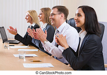 Portrait of successful applauding young people sitting in line in black comfortable chairs at the table with monitor, papers and glasses of water on it