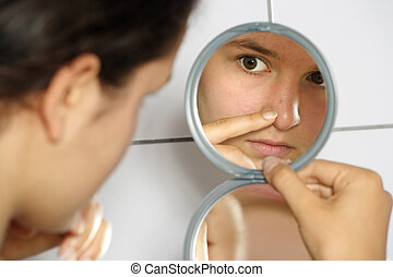 Acne - Young teenage female holding a mirror looking at her...