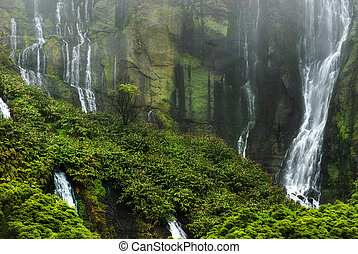 waterfalls above small lake, mountains covered in fog