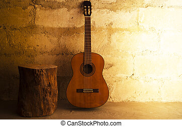 Acoustic guitar on old wall and stump with copyspace