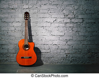Acoustic guitar leaning on grungy wall