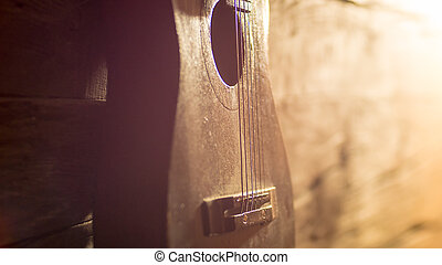 Acoustic guitar leaning on grungy wooden wall