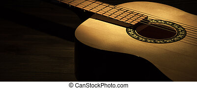 Acoustic guitar on a wooden table lit by a spotlight. Side view.