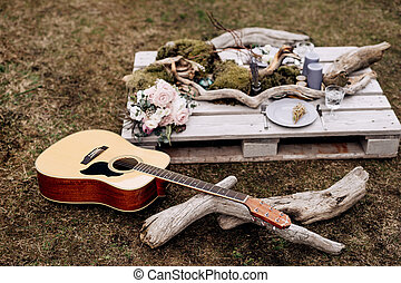 Acoustic guitar on the grass against the background of a wooden stand with items for decoration.