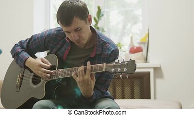 acoustic guitar played by a man. man playing acoustic guitar slow motion video. in the room sits on lifestyle the couch. man and guitar concept