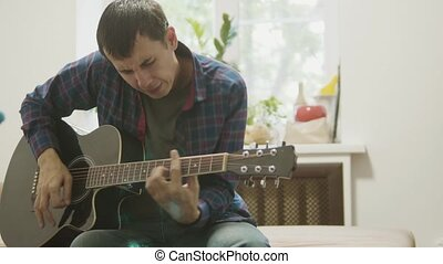 acoustic guitar played by a man. man playing acoustic guitar slow motion video. in the room sits lifestyle on the couch. man and guitar concept