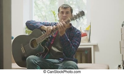 acoustic guitar played by a man. man playing acoustic guitar slow motion video. lifestyle in the room sits on the couch. man and guitar concept