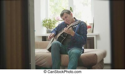 Acoustic Guitar Playing. Men Playing Acoustic Guitar Close Up slow motion video. in the room sits on the couch lifestyle. man and guitar concept