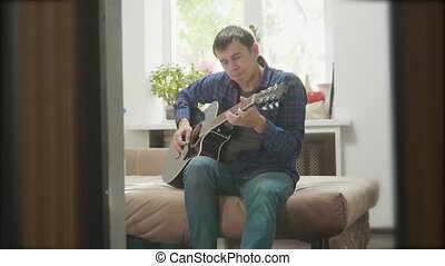 Acoustic Guitar Playing. Men Playing Acoustic Guitar Close Up slow motion video. in the room sits on lifestyle the couch. man and guitar concept