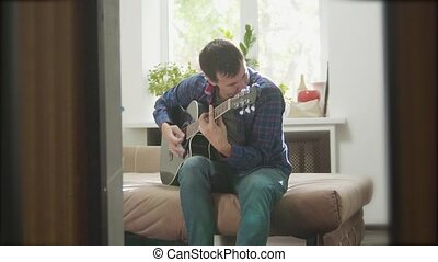 Acoustic Guitar Playing. Men Playing Acoustic Guitar Close Up slow motion video. in the room sits on the couch. lifestyle man and guitar concept