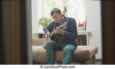 Acoustic Guitar sings Playing. Men Playing Acoustic Guitar Close Up slow motion video. in the room sits on the couch. man and lifestyle guitar concept