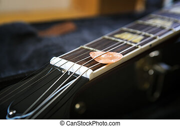 Acoustic Guitar With Piectrum In Dark Background