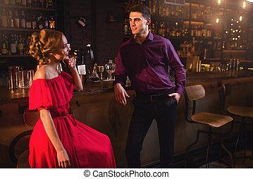 Acquaintance in bar, woman flirts with man - Acquaintance in...