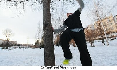 Acrobat athlete in winter park - work out parkour - a tracer...