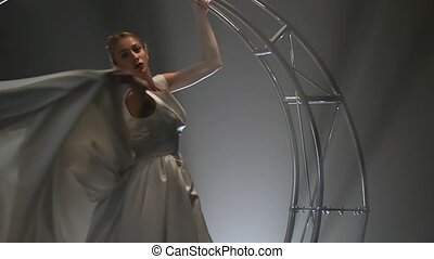 Acrobat in a white dress performs movements on a metal...