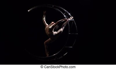 Acrobat rotates on a metal structure in a vertical string....