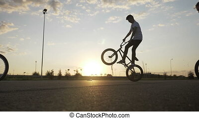 Acrobat young bikers squad doing ollie hop tricks on bikes with summer sunset in background in slow motion entertainment biking concept
