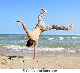 Acrobatic boy at beach.