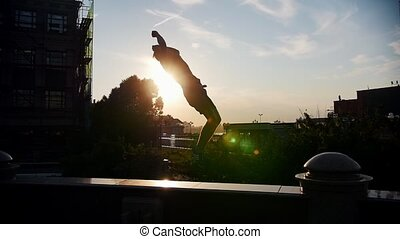 Acrobatic man performing a flip on a stand outside - sunset....