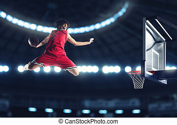 Acrobatic slam dunk of a basket player in the basket at the stadium