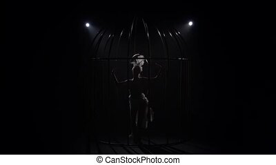 Acrobatics on a rotating hoop in a cage in a dark room. Black background. Silhouette. Slow motion