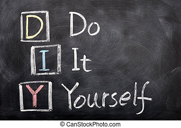 Acronym of DIY for Do It Yourself written with chalk on a blackboard