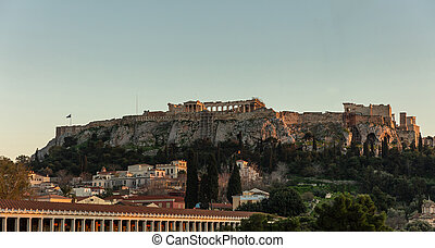 Acropolis of Athens Greece rock and Parthenon on blue sky background in the evening.