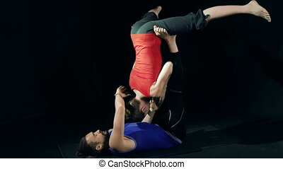 Acroyoga Practice - Couple practicing acroyoga, woman...