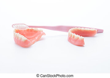 Acrylic dentures with toothbrush on white background