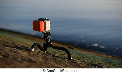 Action camera in plastic case on tripod near blue water