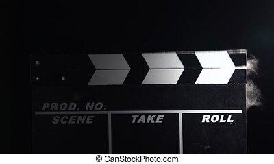 Action movie clapboar in dusk . Close up. Black background -...